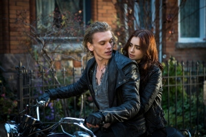 Clary (Lily Collins) rides off with Jace (Jamie Campbell Bower) in Screen Gems' fantasy-action THE MORTAL INSTRUMENTS: CITY OF BONES.